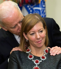Joe Biden sniffing a woman's hair with his hands on her shoulders