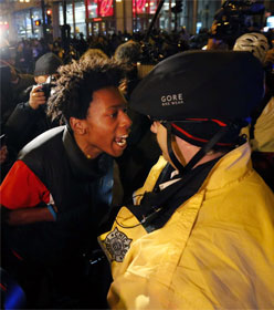 Black protester yelling at white cop, neither wearing a mask