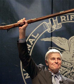 Charlton Heston hoisting rifle before 2000 NRA convention