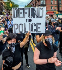 "Marching protestor holding ""Defund the Police"" sign"