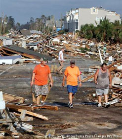 Three men walking through town destroyed by hurricane