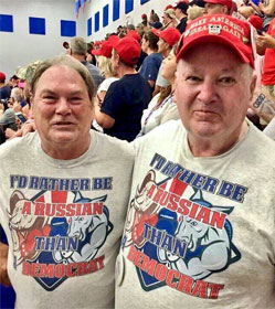 "Two men at a Trump rally wearing ""I'D RATHER BE A RUSSIAN THAN A DEMOCRAT"" t-shirts"
