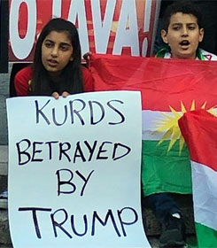 "Girl holding sign, ""Kurds betrayed by Trump"""