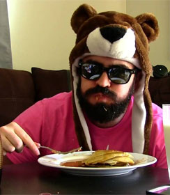 Man in dark glasses eating pancakes