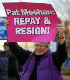 "Female protester holding a sign, ""Pat Meehan: REPAY & RESIGN!"""