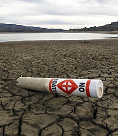 """No boats"" sign on parched lakebed"