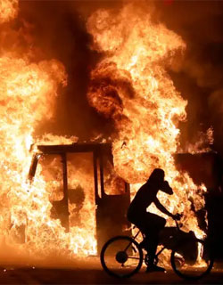 Man on bicycle riding past building in flames, Kenosha WI