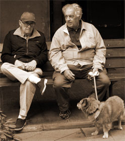 Two men sitting and talking, one with a dog on a leash